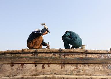 青岛:渔港修船人敲敲补补30年
