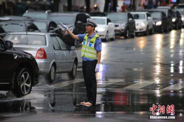 青島暴雨 交警赤腳指揮交通
